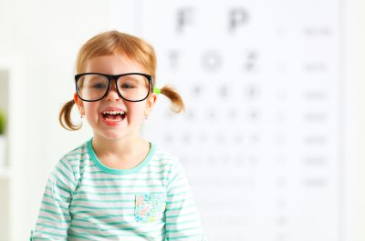 concept vision testing. child girl with eyeglasses at the doctor ophthalmologist ** Note: Visible grain at 100%, best at smaller sizes