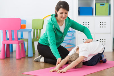Child during physiotherapy exercises and woman instructor