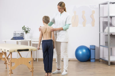 Doctor correcting small boy's body posture standing in well equipped physiotherapist office