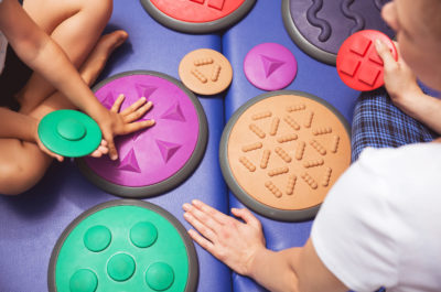 Girl's and therapist's hands touching the various shaped mat
