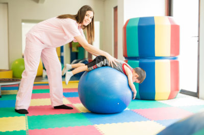 Portrait of a happy therapist working on some physical therapy on a child using a stability ball