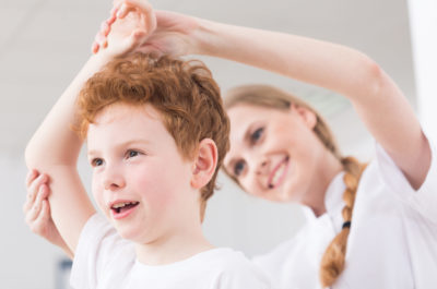 Pretty happy physiotherapist glad of results in boy's physiotherapy of injured shoulder