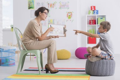 Young woman holding a picture conducting child's psychological test